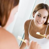 Woman in bathroom brushing teeth and smiling